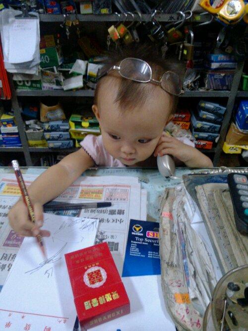 米乐模仿爷爷听电话写字